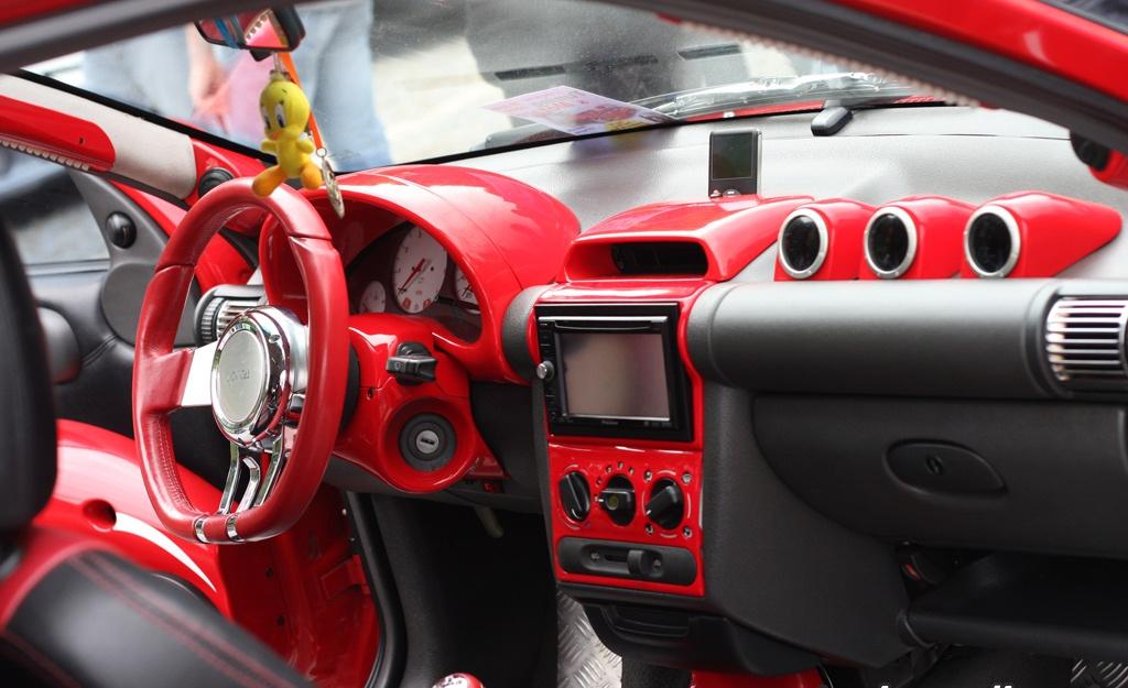 En su interior, volante y pomo de cambios deportivo. Tablero laqueado en  color rojo con gris. Pantalla incorporada. Butacas tapizadas combinando con  paneles