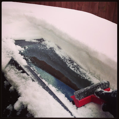 scraping snow off the car
