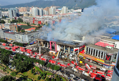 Smoke billowing from a shopping mall in the Shijingshan district in Beijing. Two firefighters died when they put out the fire that broke out in the early morning of October 11