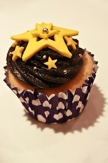 Cupcake with black buttercream swirl, yellow fondant stars and silver balls