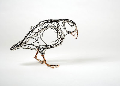 Escultura de pájaro hecha con cables.