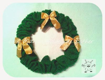 corona navideña realizada a crochet y decorada con lazos dorados