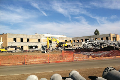 Front of building pictured with 'B' wing demolished, windows removed, rubble, and heavy equipment in the foreground.