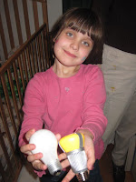 child holding incandescent and LED lightbulbs