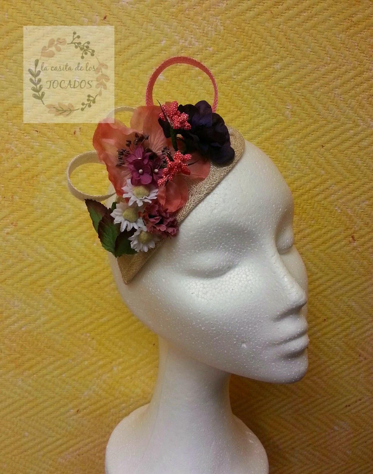 tocado campestre realizado con flores variadas en tamaño, forma y color, que incluye adornos de sinamay sobre base natural de lágrima