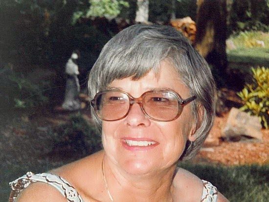 Photo of an adult white woman wearing sunglasses, with short grey hair, smiling