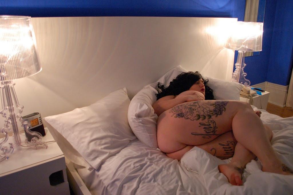 Faye Daniels allongée nu sur le côté sur un lit