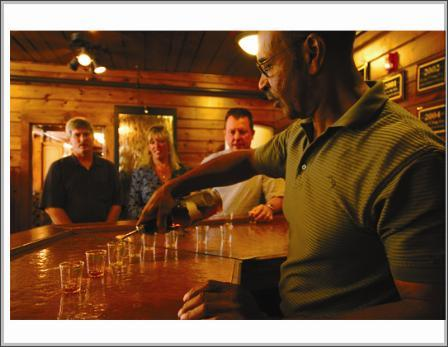 a tour guide pouring bourbon samples into glasses on a wood counter for three guests to sample at buffalo trace distillery