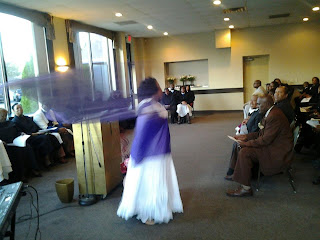 copyright Katina Davenport 2012, Praise dancer in white dress with purple tunic and purple flag.