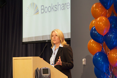 Betsy Beaumon at a podium with balloons and Bookshare logo on a screen.