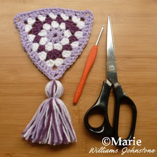 Crocheted triangle complete with tassel decoration