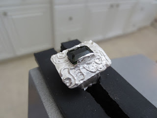 fired metal clay ring in a vise, ready to set the tourmaline