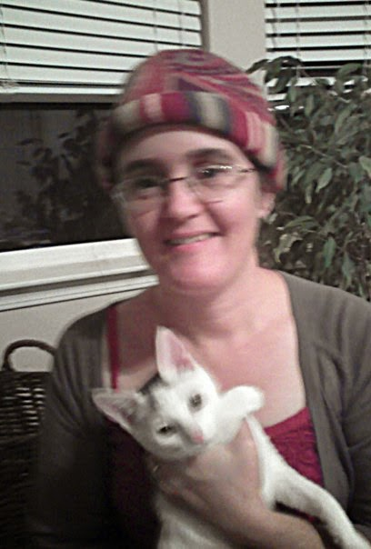 Cynthia Parkhill wearing a brimless burgundy-and-gold paisley fleece cap while holding Gizmo, a white kitten with an asymmetrical black-tabby splotch between his ears. The cap is rolled up to display the brim, in burgundy, gold and green-striped fleece fabric.