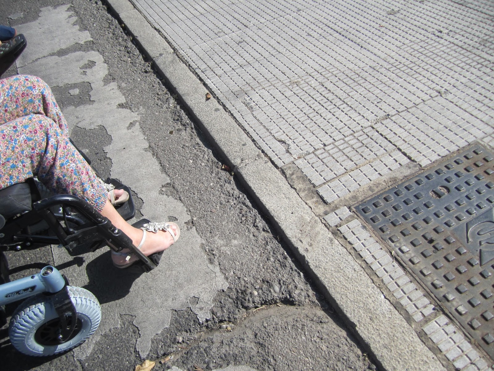 Imagen de persona usuaria de silla de ruedas justo antes de superar el desnivel.