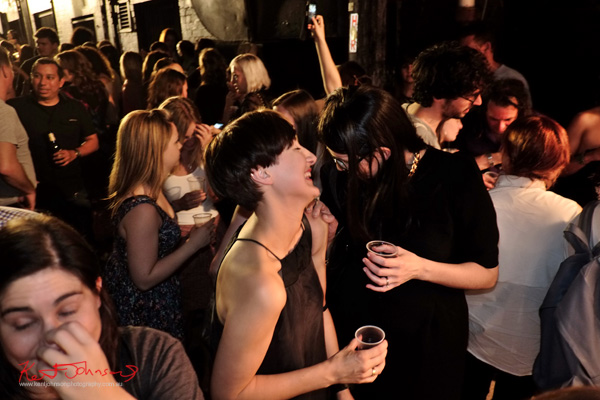 friends in animated conversation now laughing, both wear black, Art Month Sydney art party Darlinghurst Sydney 2013