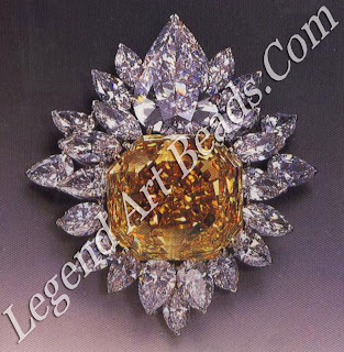 A brooch with a fancy yellow diamond of 107 carats, surrounded by 23 pear shaped marquise diamonds (1988).
