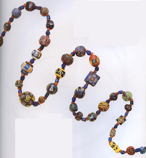 Necklace: A wide variety of mosaic and other patterned glass beads interspersed with small carnelians and blue glass corner less cubes. Beads shown date from the Phoenician through early Islamic periods (c. 400 B.C.-A.D. 900). Center bead: diameter 1.9 cm. Private collection