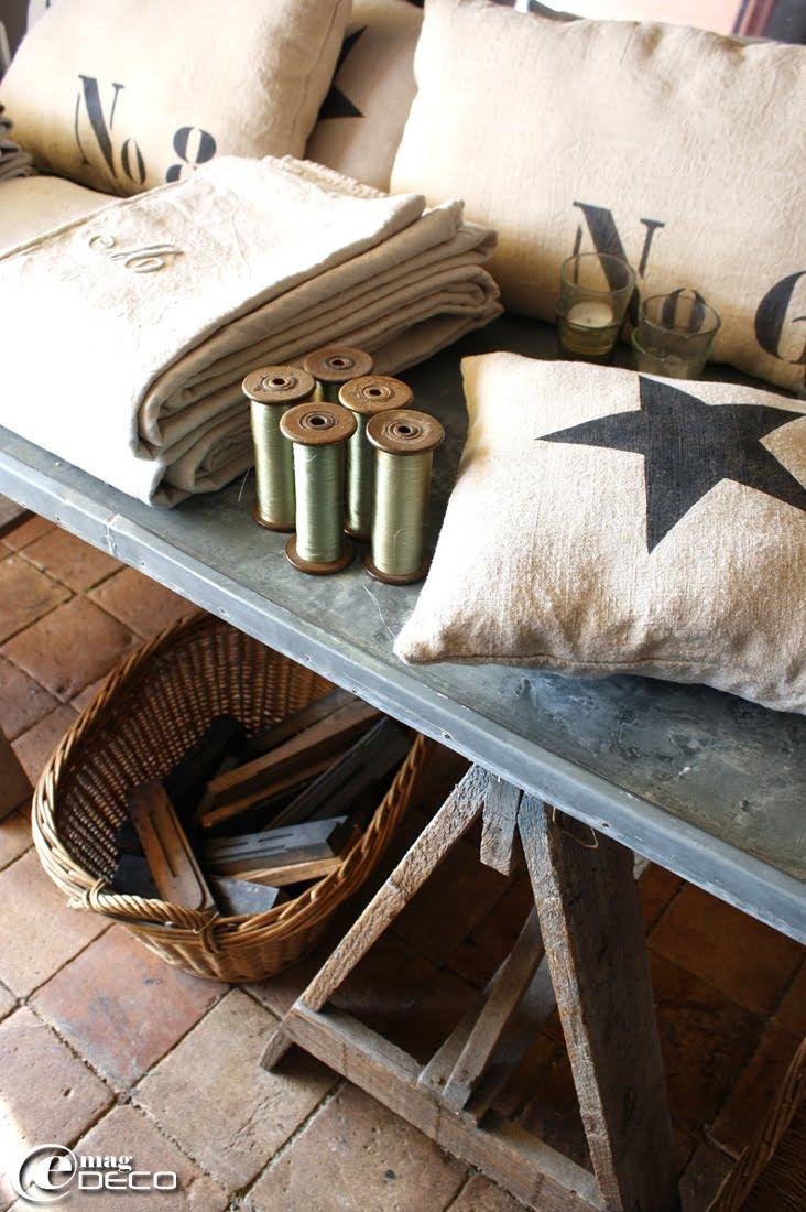Lettres d'imprimerie dans un panier en osier et des coussins peints au pochoir, créations Florence Bouvier