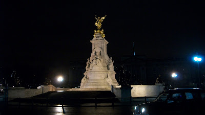 The golden monument to Queen Victoria, lit up at night in front of Buckingham Palace.
