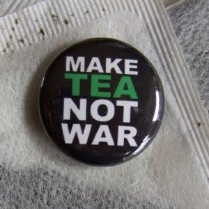 button reads make tea not war