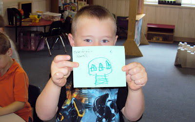 One boy shows off his picture of his home