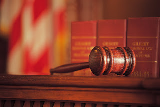 Photo illustration of a judge's bench with law books and gavel.