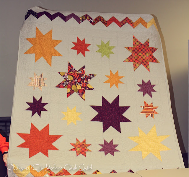 Anges Star Quilt in autumn colors with a autumn rainbow zig zag at the top and bottom.  Gray background and binding.