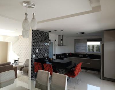 A sala de jantar deste sobrado atua como pólo de integração com a sala de estar à esquerda, cozinha ao centro e varanda gourmet à direita. O balcão possui duas alturas de tampos e funciona como mesa de refeição no cotidiano.