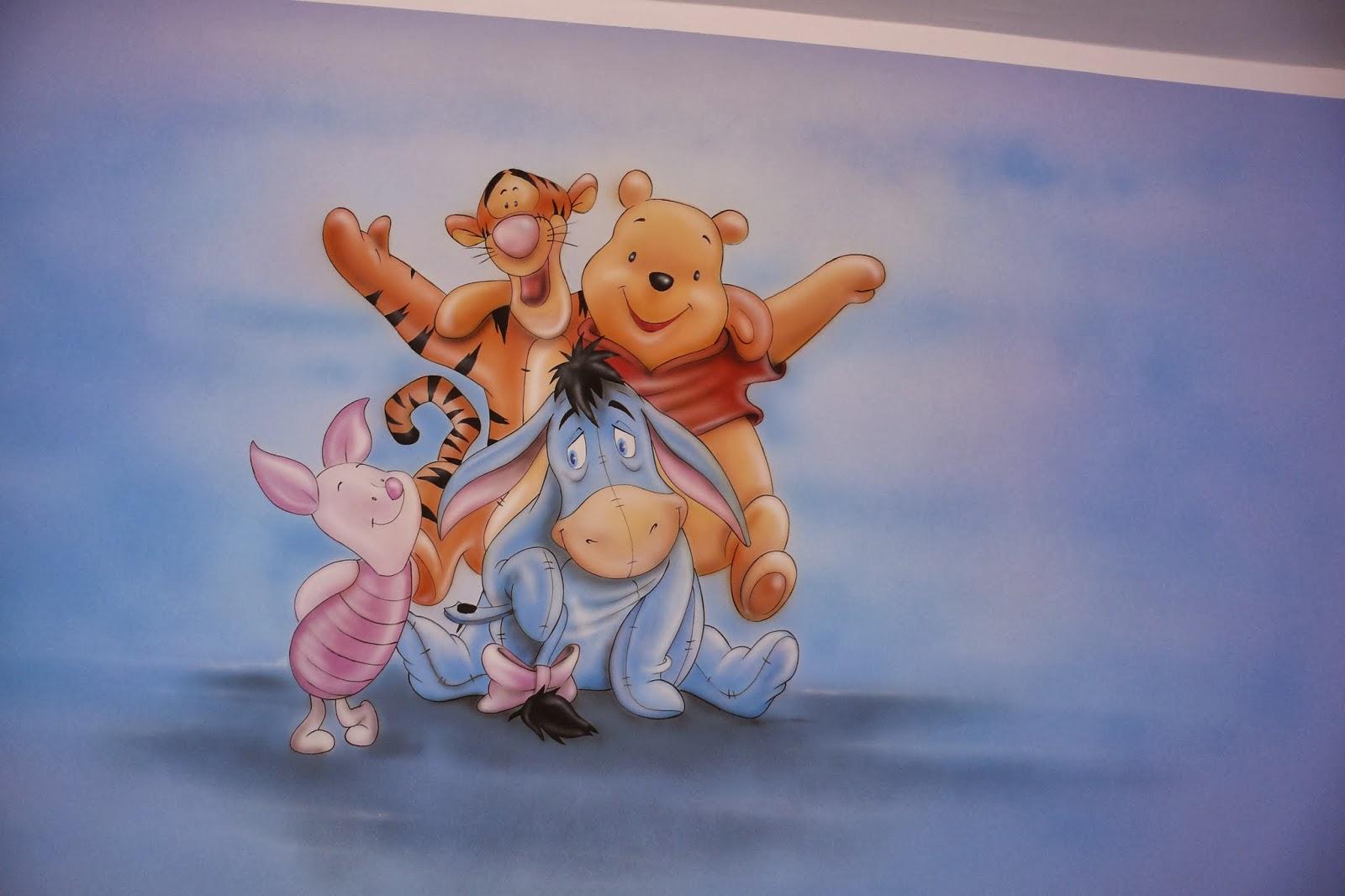 Artystyczne malowanie ściany, praca przedstawia postacie z Kubusia Puchatka, motyw malowany na ścianie