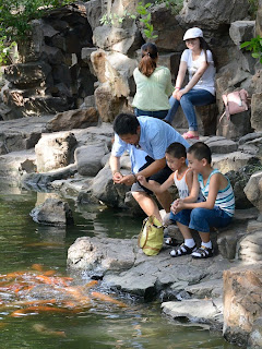 Children feeding fish at Yu Garden in Shanghai