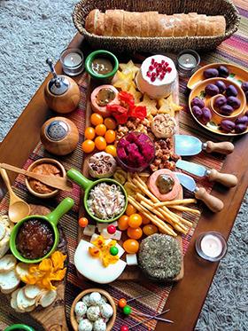 Uma tábua de queijos com medalhões de salmão e flores comestíveis