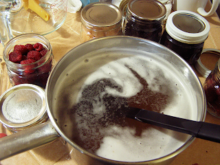 Hot Honey Syrup in Pan next to Berries in Jars