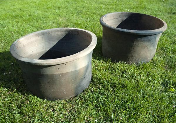 Två mörka lerkrukor som står på gräs.