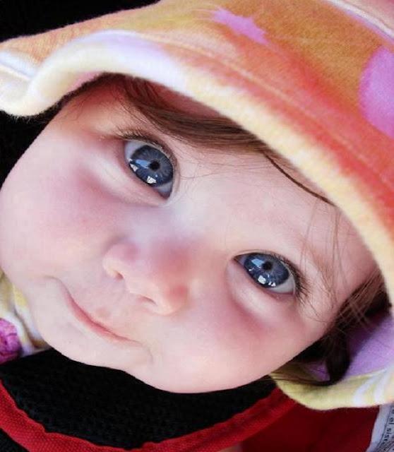 un adorable bébé qui a les yeux bleu, magnifique