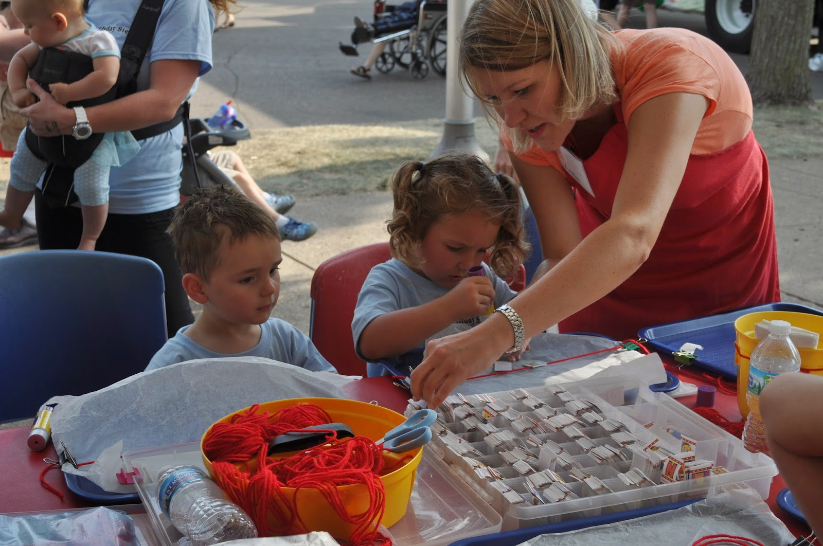 photo of Alphabet Fair volunteer helping two children make name necklaces