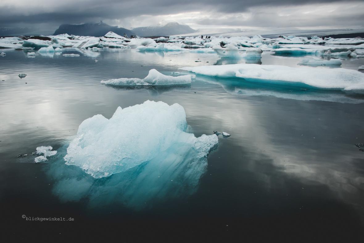 blau schimmernde Eisberge vor grauem Himmel