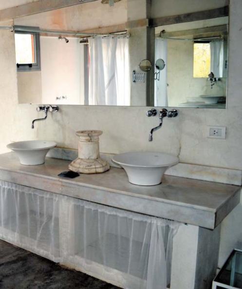 la elegancia dela encimera de mrmol destaca con la simplicidad del cemento pulido del suelo y las paredes