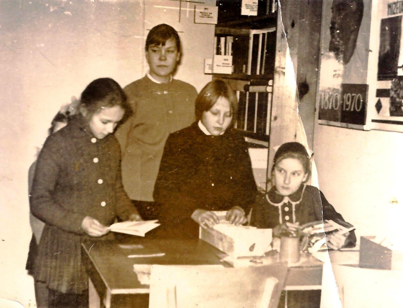 Skolnieces bibliotēkā pie galda
