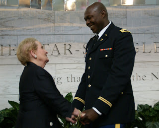 Madeleine Albright, former Secretary of State, greets new U.S. citizen Olugbenga Olufemi Obasanjo (U.S. Army)