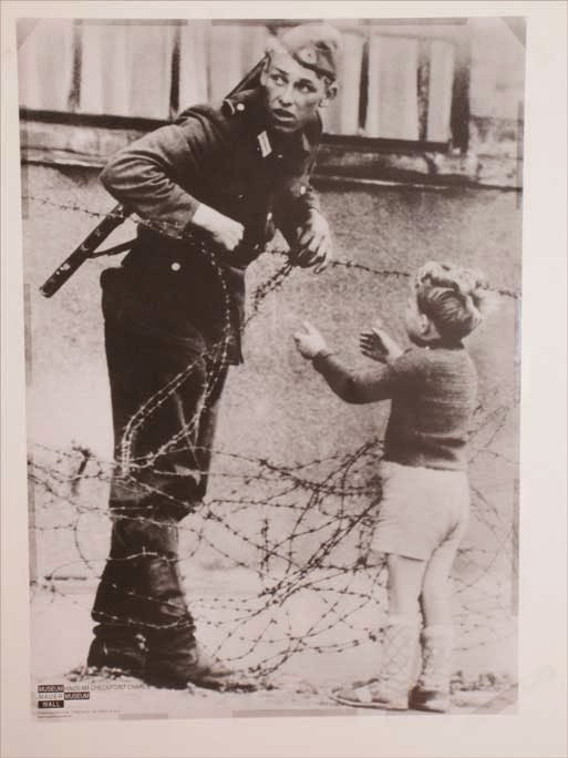 East German soldier helps a little boy
