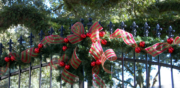 Striped deco mesh decorates an iron gate for the holidays