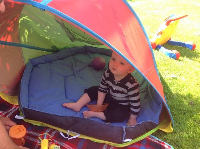 baby sat in tent in garden with blue padded base from playpen