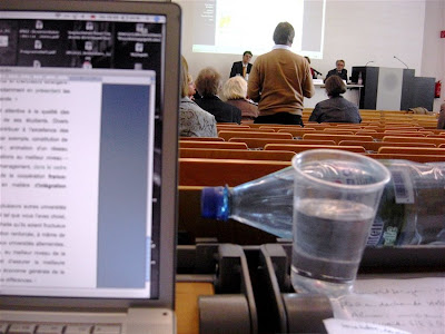 Kein Blick aufs Mundbild: Unihörsaal, viele Reihen, Sprecher, die uns den Rücken zukehren, ausgeklappter Laptop, daneben drohen Wasserflasche und gefüllter Plastikbecher