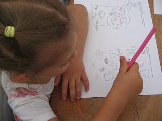 Törpmanós feladatlapot old egy copfos kislány, amin be kell karikázni illetve színezni a ruhákat évszaktól függően.