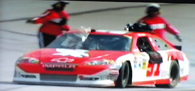#51 Kurt Busch pulls away from safety workers with a bag on the roof