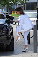 Kim Kardashian dressed in white and filling up her Rolls Royce