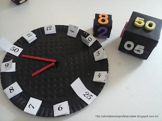 Relógio feito com prato de papelão. Fundo pintado de preto e as horas representadas em pedacinhos de papel  branco, dobrados. A parte de cima, com números de 1 a 12, representam as horas e dentro do cartão, números de 5 em 5, representam os minutos.  Os cubos marcam 8 horas e 50 minutos.