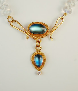 gold colored clasp with an oval and pear shaped white stone with strong blue highlights