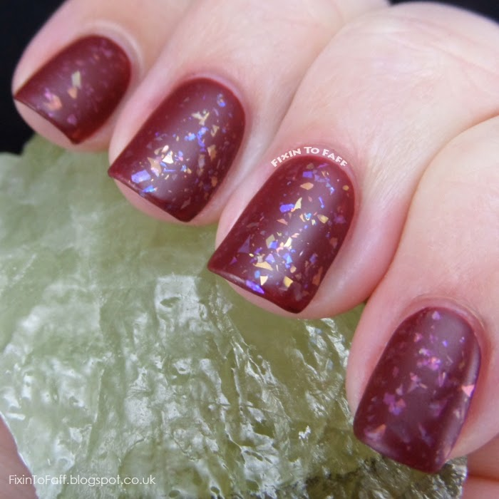 Matted nail art look of flakies over oxblood polish.