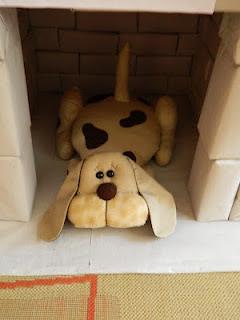Cachorro de brinquedo dentro de casinha para cães e gatos, feita de materiais recicláveis